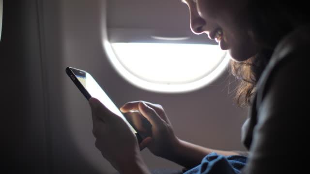 vidéos et rushes de femme à l'aide de smart phone sur avion - voyage d'affaires
