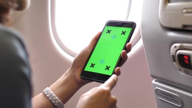 vidéos et rushes de téléphone intelligent à l'aide de femme sur avion avec écran vert, gros plan - couche alpha