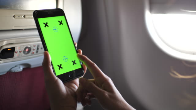 Woman Using Smart phone on Airplane with Green screen, Close-up
