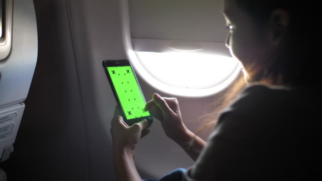 woman using smart phone on airplane with green screen - web browser stock videos & royalty-free footage