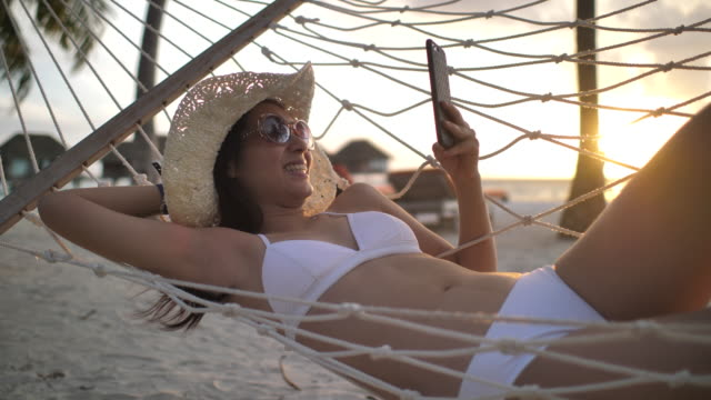 woman using smart phone on beach in hammock - resting stock videos & royalty-free footage