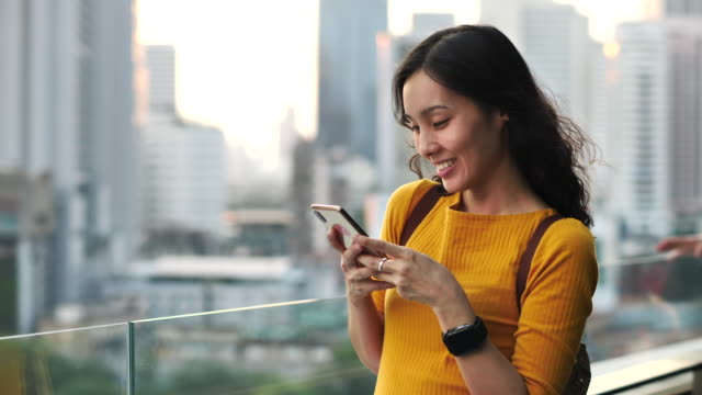 vídeos de stock, filmes e b-roll de mulher usando telefone inteligente no rooftop in city - telhado