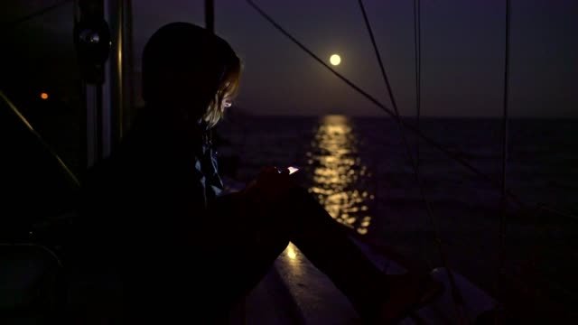 4k woman using smart phone on sailboat at night with tranquil full moon shining on ocean, real time - yachting stock videos & royalty-free footage