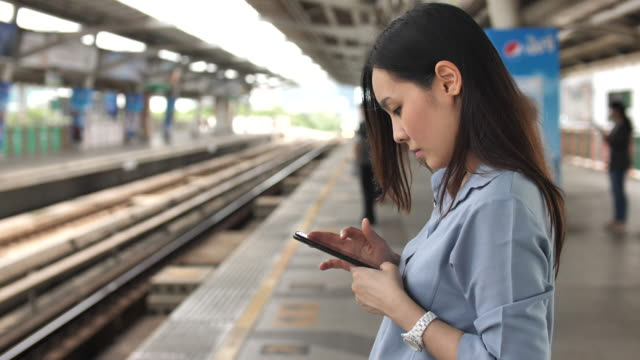 woman using smart phone on the metro station - commuter stock videos & royalty-free footage