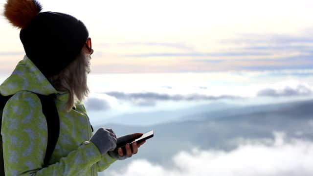 vídeos de stock, filmes e b-roll de mulher usando telefone inteligente no topo da montanha - sistema de posicionamento global