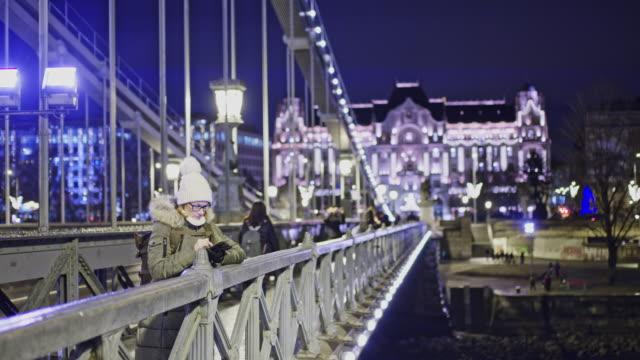 vidéos et rushes de woman ms à l'aide de téléphone intelligent sur pont urbain de nuit, budapest, hongrie - budapest