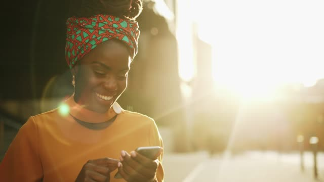 woman using smart phone, sunset, smiling - using phone stock videos & royalty-free footage