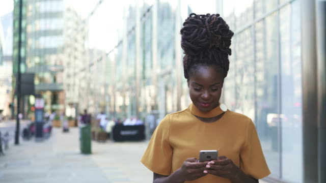 woman using smart phone, text messaging, responding. - locs hairstyle stock videos & royalty-free footage