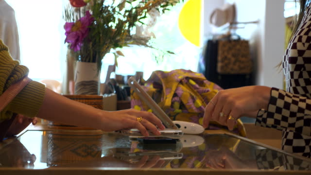 ms pan woman using smart phone to pay for purchase while shopping in clothing boutique - checkout stock videos & royalty-free footage