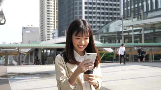 kvinna som använder smart phone - east asian ethnicity bildbanksvideor och videomaterial från bakom kulisserna