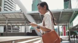 Woman using Smart phone walking on the street