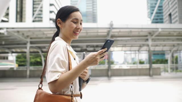 frau mit smartphone zu fuß auf der straße - street name sign stock-videos und b-roll-filmmaterial
