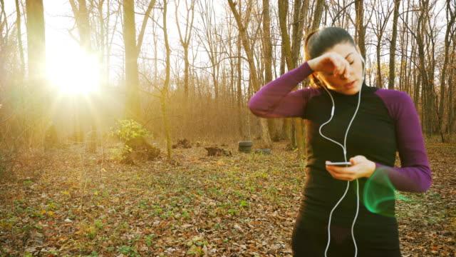 vidéos et rushes de femme à l'aide de téléphone intelligent tout en tapotant. - casque audio