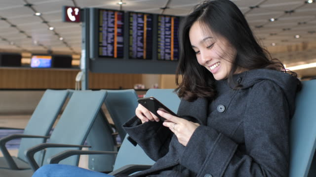 woman using smart phone while waiting boarding at departure area at the airport - accessibilità video stock e b–roll