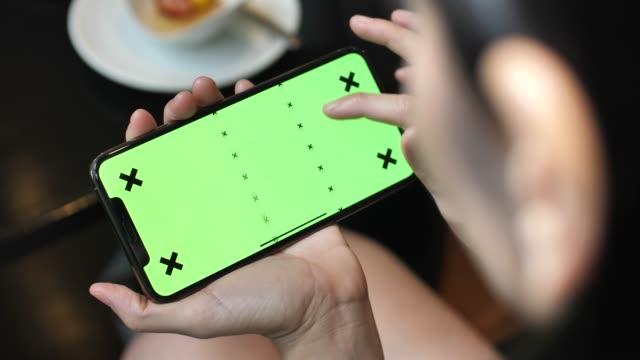 frau mittels smartphone mit chroma-key für unterhaltung, horizontal - über die schulter stock-videos und b-roll-filmmaterial