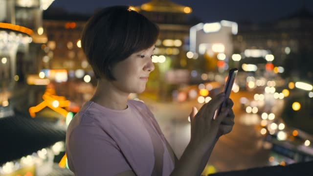 woman using smart phone with city street at night - chinese ethnicity stock videos & royalty-free footage