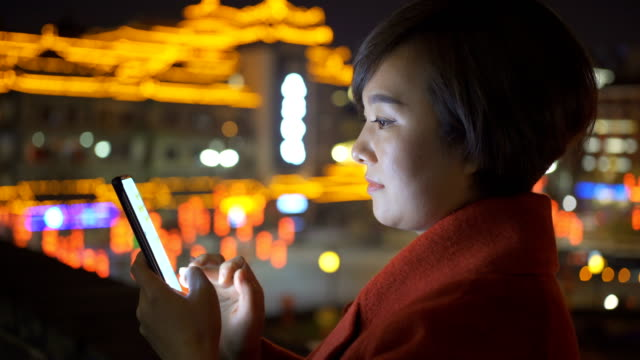 woman using smart phone with cityscape during chinese spring festival - profile stock videos & royalty-free footage