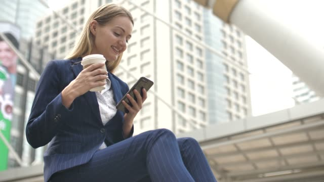 woman using smart phone with coffee cup in city - businesswear stock videos & royalty-free footage