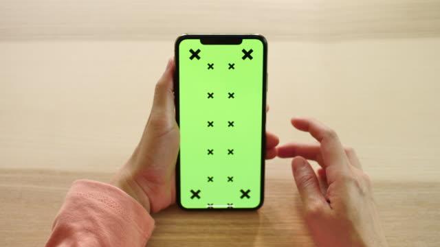 グリーンスクリーンディスプレイでスマートフォンを使用している女性 - スクロール点の映像素材/bロール
