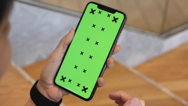 グリーンスクリーンでスマートフォンを使用している女性 - スクロール点の映像素材/bロール