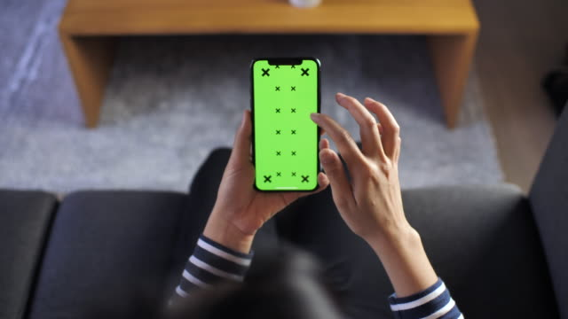 frau mittels smartphone mit greenscreen, pov - iphone stock-videos und b-roll-filmmaterial