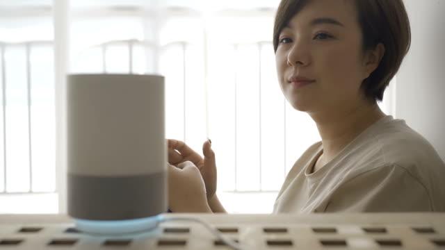 stockvideo's en b-roll-footage met vrouw die slimme sprekers in huis gebruikt - luidspreker