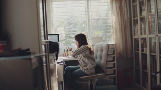 ホームオフィスでスマートウォッチを使用している女性 - 家の中点の映像素材/bロール