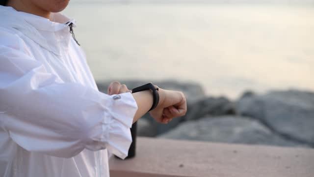vídeos y material grabado en eventos de stock de mujer usando monitor de fitness reloj inteligente y podómetro junto al mar al atardecer para seguir el entrenamiento al aire libre - chaqueta
