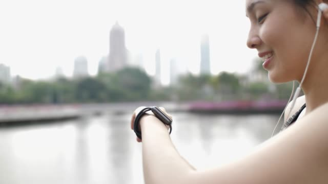 woman using smart watch for monitoring her running performance on smartwatch, fitness tracker - fitness tracker stock videos and b-roll footage