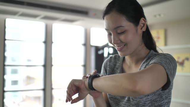 woman using smart watch while exercising for check plus - checking the time stock videos & royalty-free footage