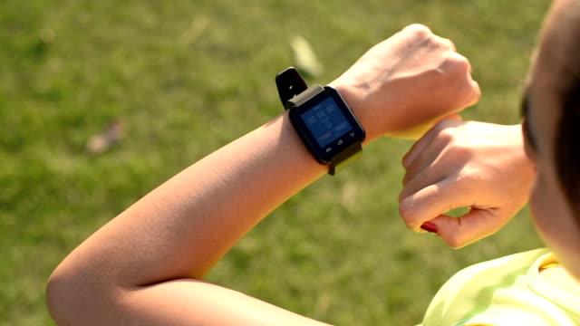 vídeos de stock e filmes b-roll de woman using smart watches before start jogging - computador utilizável como acessório