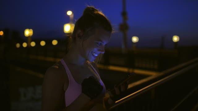 vídeos de stock, filmes e b-roll de woman using smartphone after freeletics fitness workout. - software de computador