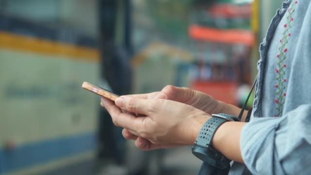 vídeos y material grabado en eventos de stock de mujer con smartphone en parada de autobús, close-up - asociación norteamericana de telecomunicaciones e internet