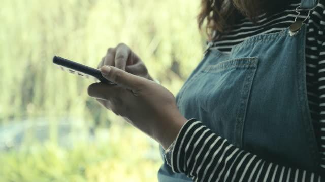 女性のコーヒー ショップでスマート フォンを使用して - 受ける点の映像素材/bロール