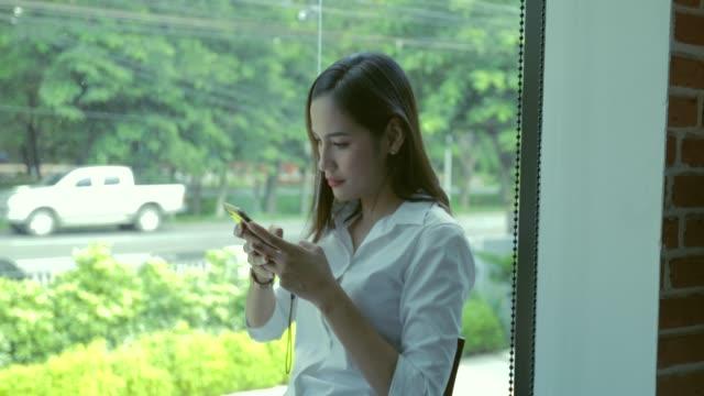 コーヒーショップでスマホを使っている女性 - 受ける点の映像素材/bロール
