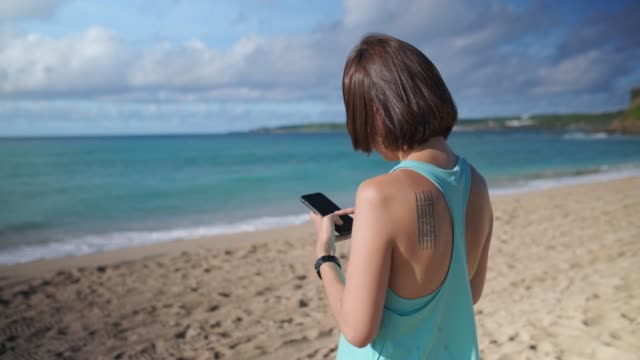 woman using smartphone by the beach - korea stock videos & royalty-free footage