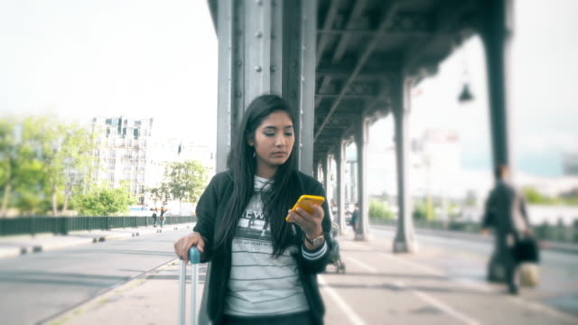 CNGLLEI1052 Woman using smartphone call a Taxi on the street