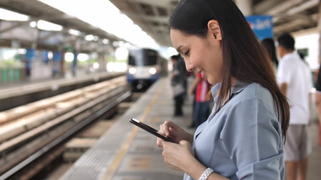 woman using smartphone for social networking on train station - ora di punta video stock e b–roll