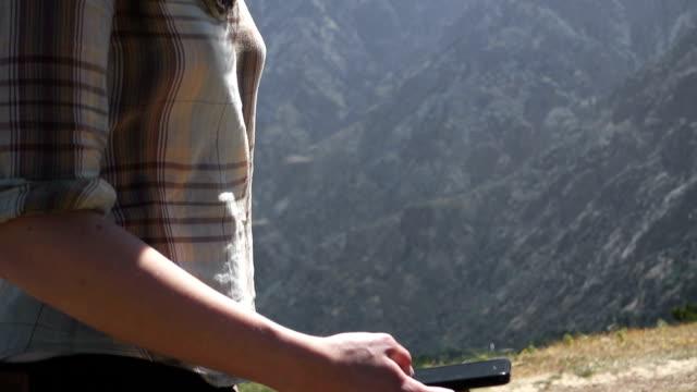 Woman using smartphone in mountain range