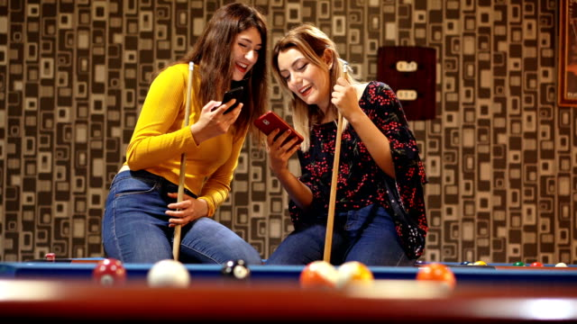 woman using smartphone in pub. snooker room background - hole stock videos and b-roll footage