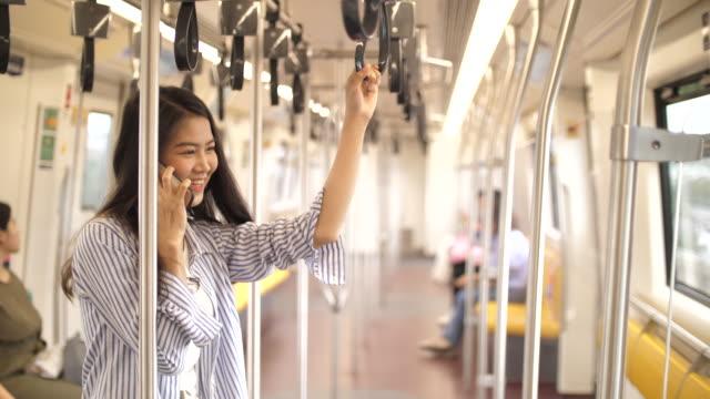 公共交通機関でスマートフォンを使用している女性 - バス停留所点の映像素材/bロール