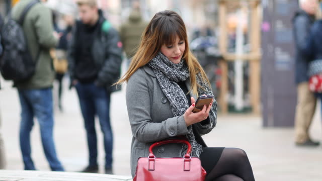 woman using smartphone in public - tights stock videos & royalty-free footage