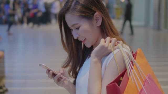 woman using smartphone in shopping mall - shopping bag stock videos and b-roll footage