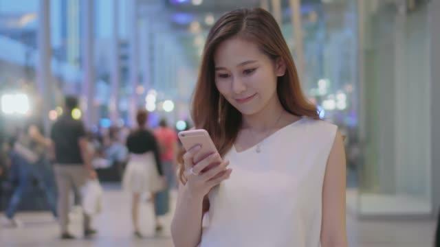 Femme à l'aide de smartphone dans centre commercial
