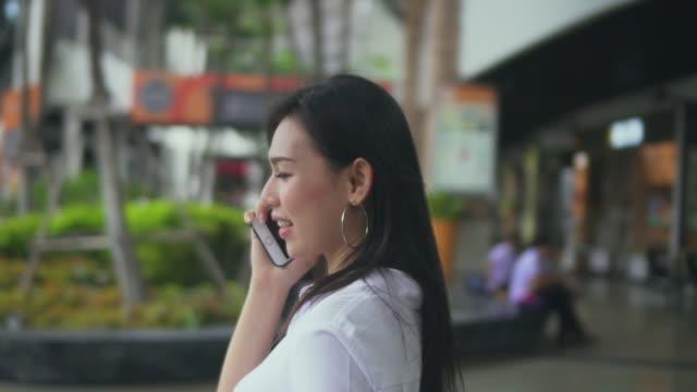 vídeos de stock e filmes b-roll de woman using smartphone in shopping mall,slow motion - vista de 360 graus