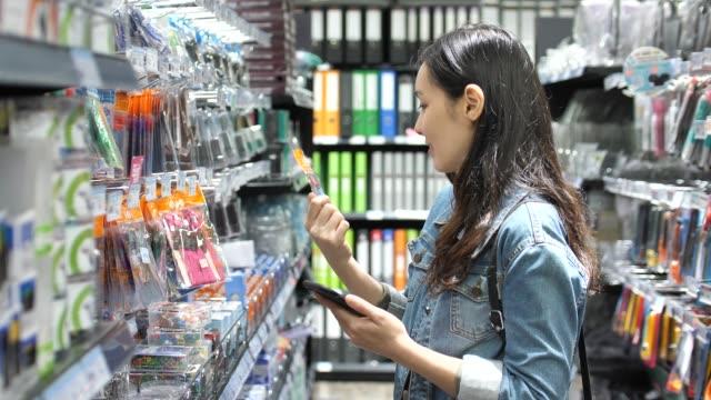 vidéos et rushes de femme à l'aide de smartphone en magasin, slow motion - marchandise