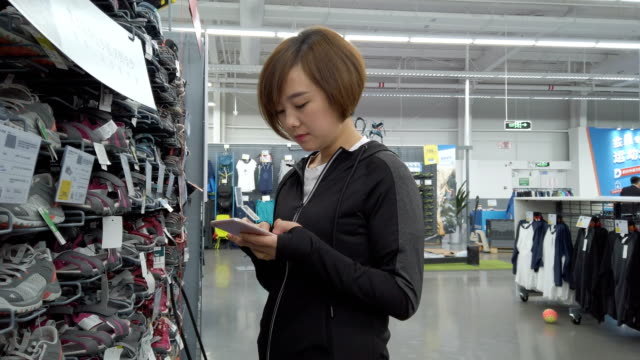 woman using smartphone in store - three quarter length stock videos & royalty-free footage