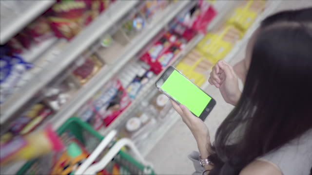 woman using smartphone in supermarket - mar stock videos & royalty-free footage