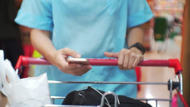 Woman using smartphone in supermarket