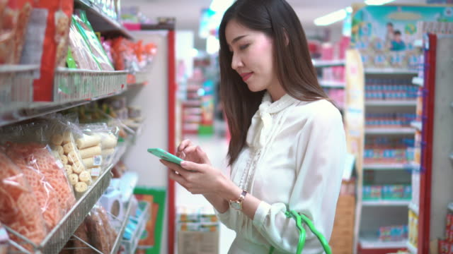 vidéos et rushes de femme à l'aide de smartphone dans un supermarché - marchandise